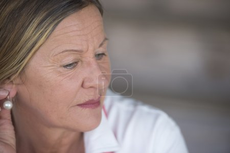 Photo for Portrait elegant attractive mature woman with sad lonely concerned depressed expression, blurred background, copy space. - Royalty Free Image