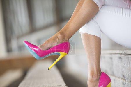 Photo pour Concept image rapprochée de la femme assise dans des chaussures à talons hauts rose sexy élégant, détendu sur le banc, espace de copie, fond flou - image libre de droit