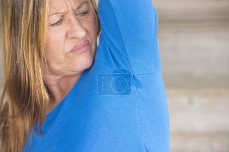 Photo for Portrait angry mature woman with smelly sweat perspiration under arm with wet moisture spot on blue shirt, blurred background, copy space. - Royalty Free Image