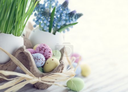 Photo for Easter decoration with small chocolate eggs, green grass and blue muscari flowers with hazy vintage editing - Royalty Free Image