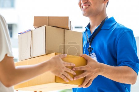 Photo for Woman accepting a delivery of cardboard boxes from deliveryman - Royalty Free Image