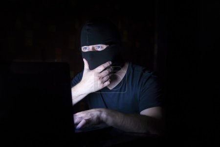 Hacker in black mask with laptop