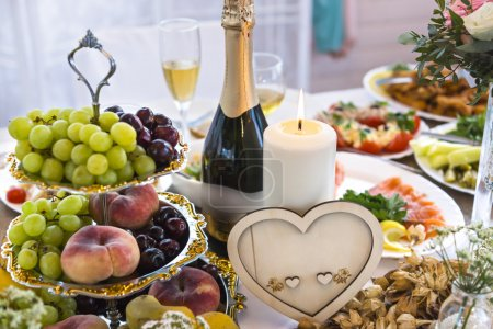 Photo pour Table de mariage avec bougie et décoration en forme de coeur et bouteille de champagne sur table de fête - image libre de droit