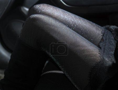 Photo pour Minces jambes sexy de jeune femme en collants brillants en voiture - image libre de droit