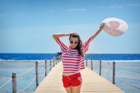 Photo pour Jeune femme pleine d'énergie sur un ponton face à la mer par une journée ensoleillée. - image libre de droit