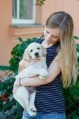 Portrét mladé ženy držící v rukou štěně Labrador