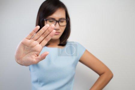 Mujer joven mostrando su negación con NO en la mano