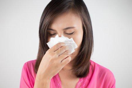 Flu cold or allergy symptom. Sick woman girl sneezing in tissue