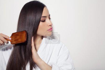 Photo pour Belle jeune femme peigner ses cheveux sains et brillants, studio blanc - image libre de droit