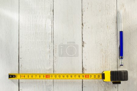 tape measure and pencil on wood