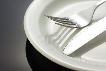 knife and fork at plate on black