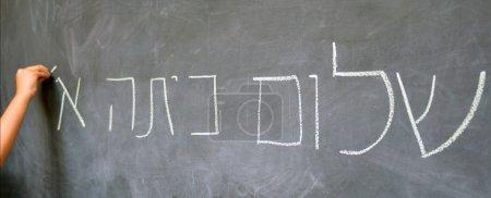 Photo pour Little child hand écrit Hello First Grade salutations en hébreu (Shalom Kita Alef) sur un tableau dans l'école primaire israélienne au début de l'année scolaire. Éducation concept photo - image libre de droit