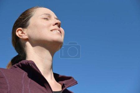 Mujer adulta feliz (mujer de 30-40 años) con los ojos cerrados al aire libre respirando aire fresco y limpio aislado en el cielo azul claro.