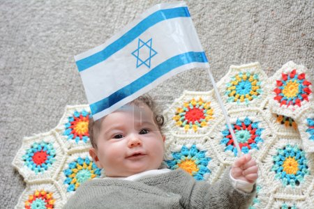 Israeli newborn baby holding the Israeli flag.