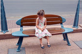 Little girl sit on a bench