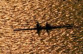 Silhouette of sportsmen on row boats