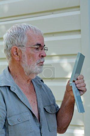 Photo pour Mature homme avec barbe grise se regarde dans le miroir extérieur - image libre de droit