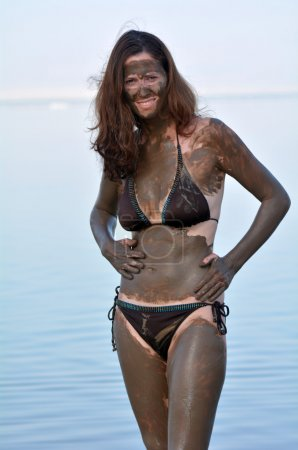 Woman enjoying the natural mineral mud sourced from the Dead Sea