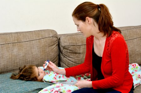 Caring mother taking care of her ill girl child