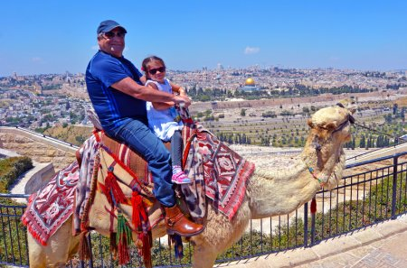 Tourists ride a camel against the old city of Jerusalem, Israel.