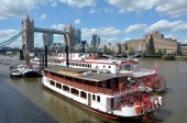 LONDON -  MAY 13 2015:P.S. Elizabethan against the Tower Bridge in London,UK. It is one of the most luxurious boats for hire on the River Thames in London choice of royalty and the rich and famous.