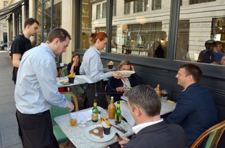 Waiters serving food and drinks to people dining in a restaurant