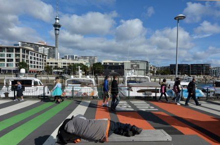 Photo for AUCKLAND - AUG 01 2015:Homeless sleep on a bench in Viaduct Harbour against Auckland skyline.In 2104 Statistics New Zealand estimated about one in 120 New Zealanders were homeless or housing deprived. - Royalty Free Image