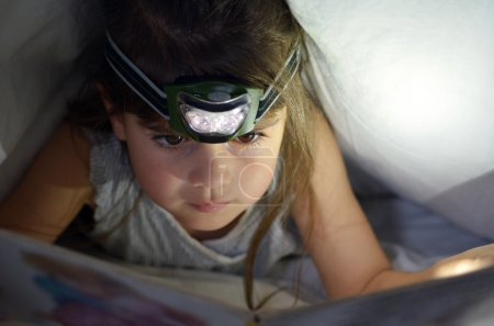 Photo pour Petit enfant (fille de 5-6 ans) lit le livre au lit sous les couvertures la nuit. Vue de face, espace de copie - image libre de droit