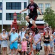 Постер, плакат: Man ride unicycle during a street performance