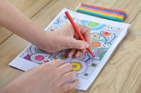 Woman hands coloring  patterns on a coloring page for stress rel