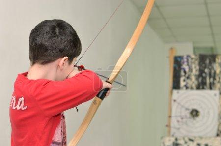 boy is shooting an arrow at