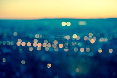 City blurring lights abstract circular bokeh on toned blue backg