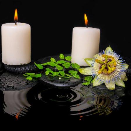 Photo pour Spa nature morte de fleurs de passiflore, fougère feuille verte avec chute et bougies sur zen pierres dans l'eau d'ondulation réflexion, closeup - image libre de droit