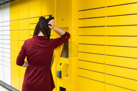 After entering the code, the teenager waits for the package to be delivered. Long wait. African braids. At the parcel lock.