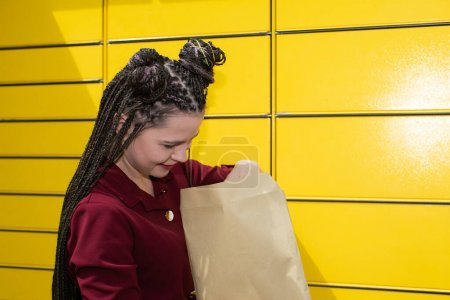 A young adult prepares a shipment in a gray envelope to be sent through a parcel machine. African braids.