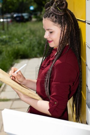 A young girl is addressing the letter while standing next to the parcel locker. Use a ballpoint pen to write on the gray letter envelope. Attractive teenage girl.