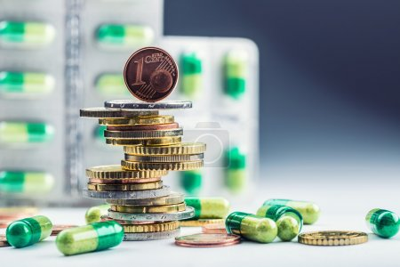 Euro money and medicaments. Eurocoins and pills. Coins stacked on each other in different positions and freely pills scattered around. Reimbursement of medicinal products in health care