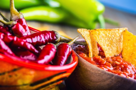 Salsa with tortilla chips and chilli peppers.Macro concept