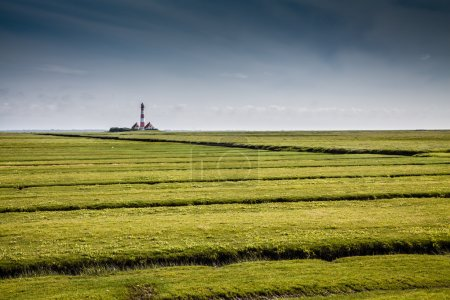 Photo for Beautiful landscape with famous Westerheversand lighthouse in the background at North Sea in Nordfriesland, Schleswig-Holstein, Germany. - Royalty Free Image
