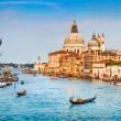 Panoramic view of famous Canal Grande and Basilica di Santa Maria della Salute in golden evening light at sunset in Venice, Italy.