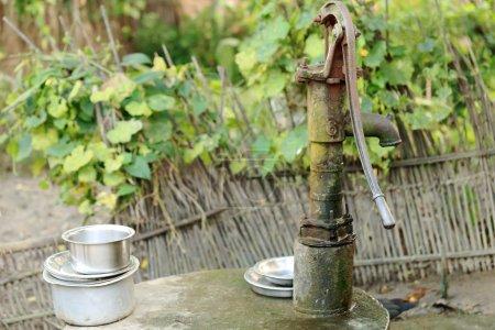 Photo pour Ancienne pompe à eau en fonte avec quelques casseroles en aluminium pour les laver sur le bosquet arrière entouré d'une clôture en roseau d'une maison traditionnelle de style Tharu dans la zone Patihani-Chitwan-Narayani-Népal . - image libre de droit