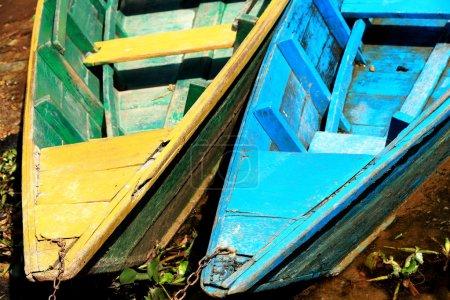 Photo pour Bateaux à rames en bois de couleur jaune-vert et bleu enchaînés à un pieu au pied de la colline Ananda sur le rivage du lac Phewa tal de 4,43 km2-784 ms.high. District de Pokhara-Kaski-Zone de Gandaki-Népal - image libre de droit