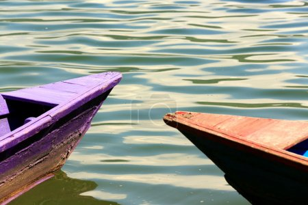 Photo for Red-blue and purple colored wooden rowboats stranded on the shore of the 4.43 km2-784 ms.high Phewa tal-lake at the foot of Ananda Hill. Pokhara-Kaski district-Gandaki zone-Nepal. - Royalty Free Image