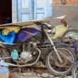 Motorbike stationed among bicycle spare parts in f...