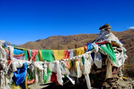 Prayer flags hanging from stone stacks. Kamba La-Tibet. 1530
