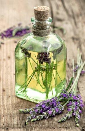 Photo pour Bouteille d'huile de lavande avec des fleurs fraîches sur fond en bois. Herbes apothicaires. focus sélectif - image libre de droit