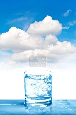 Photo pour Eau pétillante en verre sur fond de ciel bleu. Boisson fraîche froide - image libre de droit