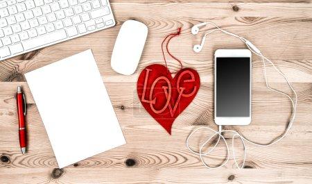 Photo pour Travail de bureau avec coeur rouge, clavier, tablette Pc, téléphone, casque. Concept de la Saint-Valentin - image libre de droit