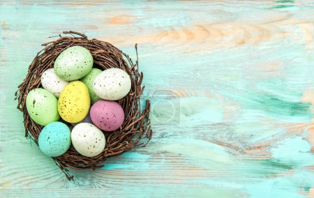 Photo for Colored easter eggs in nest on rustic wooden background. Festive decoration - Royalty Free Image