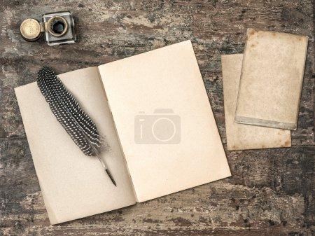 Foto de Libro abierto, herramientas de escritura vintage pluma pluma y tintero sobre fondo con textura de madera. Tonificada de estilo retro imagen - Imagen libre de derechos